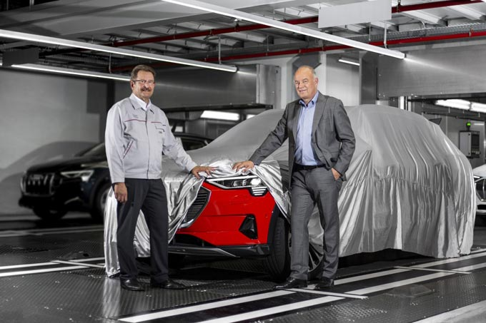 Peter Kössler, Board of Management Member for Production and Logistics at AUDI AG and Chairman of the Board of Directors of Audi Brussels (on the right), peers the first Audi e-tron models from series production. He is accompanied by Patrick Danau, Managing Director of Audi Brussels.
