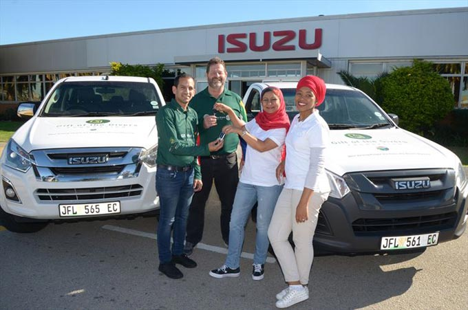 Vuyiseka Nyembezi, (right) Isuzu Motors South Africa Internal Communication and PR Officer and Ali Sablay, (left) Gift of the Givers Western and Eastern Cape Project Manager help distribute food parcels to the community of Rocklands near Uitenhage. Behind them are Gift of the Givers volunteers, Trudy Nel (middle) and Lizette Ferreira.