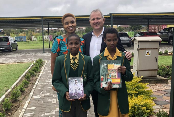 Learners from Inxiweni Primary School, Luthando Mvinjelo (left) and Siyasanga Zenzile (right), pictured with some of the books donated by Goodyear South Africa. Standing with them is Goodyear South Africa Group Managing Director, Darren Hayes-Powell, and Ruth Tabu, Inxiweni Primary School Principal.
