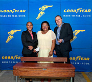 Goodyear Managing Director, Darren Hayes-Powell (right), Group Communications Manager, Nonkosi Dyantyi (left) and Stephen Nkomo Primary School Principal, Zoliswa Njiyela with one of the refurbished desks.